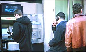 People at a cash machine
