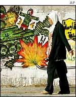 A woman walks past graffiti commemorating an attack on an Israeli tank