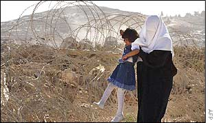A mother lifts her child through barbed wire placed by Israeli soldiers