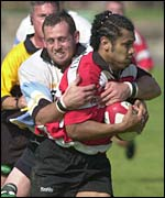 Caerphilly's Sione Tuipolotu is tackled by Ebbw's Ockert Booyse