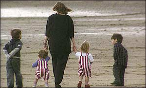Mother and family walk on a beach