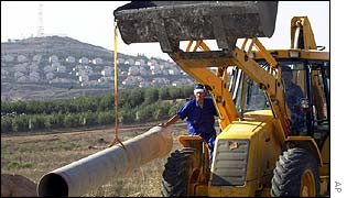 Bulldozer works on Lebanese water project with Metulla settlement in the background
