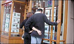 A couple looking in an estate agents window