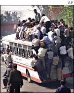 Crowd board a bus on both the inside and outside