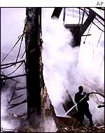 A firefighter trying to contain the smouldering section of the factory