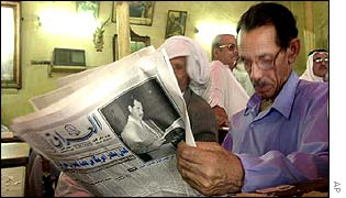 Man reading newspaper Al-Iraq newspaper in Baghdad