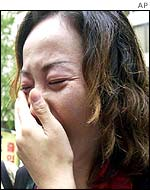 Unidentified family members of a Japanese kidnapped by North Korea weep during a protest