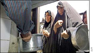 Iraqi women receive monthly food rations from a local mosque in Baghdad
