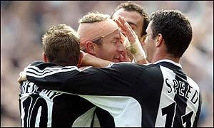 Shearer (centre) is mobbed after Newcastle's second