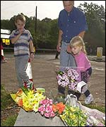 Children place flowers near the police road block, Yateley Heath, Hampshire