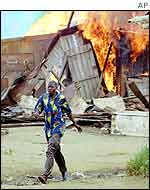 Man from migrant workers district in Abidjan walks past blazing home