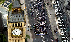 Marchers walk next to Houses of Parliament