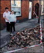 Pat Battison and daughter Sophie, 9, survey their smashed chimney