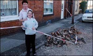 Pat Battison and daughter Sophie, 9, survey their smashed chimney in Bloxwich, West Midlands