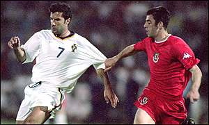 Mark Delaney in action against Portugal's Luis Figo