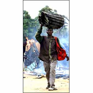 A man carrying sheets of corrugated iron  [picture: AP]