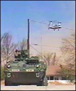 An armoured personnel carrier and helicopter in recent war games