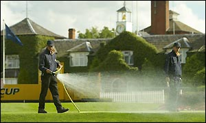 Ground staff spray the green at the tenth hole