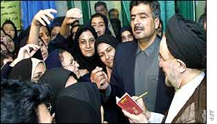 President Khatami (right) signs autographs for schoolgirls