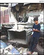 A boy beside his father's ruined workshop in Gaza