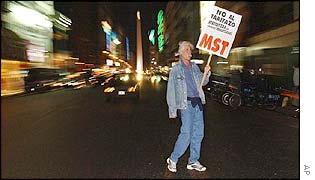 A demonstrator carries a sign reading