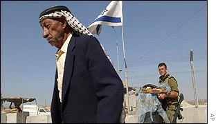 An elderly Palestinian man walks past a checkpoint and a nervous Israeli soldier