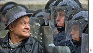 Elderly man looks on as riot police block protesters