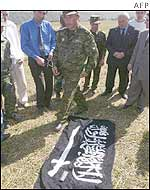 Russian officials looks at a flag seized from Chechen rebels