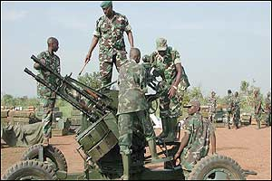 Rwandan soldiers dismantle a four-barrel anti-aircraft gun in the eastern Congolese town of Kongolo