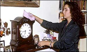 A woman dusting a clock