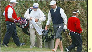 Furyk has to roll up his trousers as he plays out of the water at the seventh