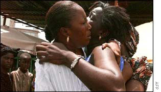 Two woman embrace as they await news of the missing passengers