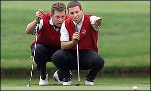 Lee Westwood and Sergio Garcia line-up a putt during their foursomes match