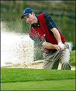 Jim Furyk plays out of a sand trap at the ninth