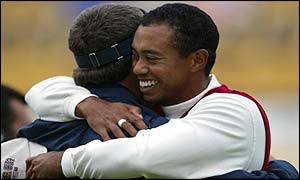 Davis Love III is congratulated by Tiger Woods after the pair win their second point of the day in the fourballs