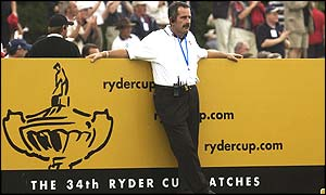 European captain Sam Torrance leans on a Ryder Cup advertising hoarding