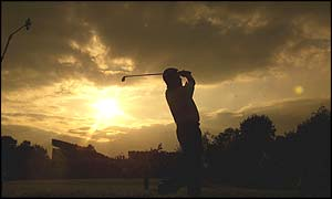Lee Westwood drives as the sun sets behind him