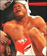 Riddick Bowe clutches his groin after being hit low by Andrew Golota