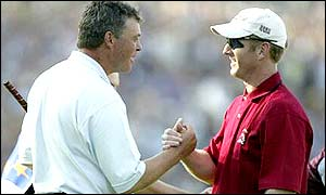 Darren Clarke and David Duval shake hands and share the honours after a close match ends level; Europe lead 11� - 9�