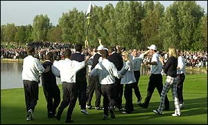 Paul McGinley is mobbed by his team-mates after winning