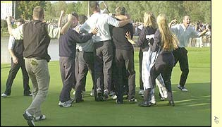 The European team swamp Paul McGinley on the green after the match winning putt