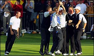 Europes Paul McGinley, third right, is mobbed by team-mates, Niclas Fasth, right, Darren Clarke, second right, Sergio Garcia, left, and caddies