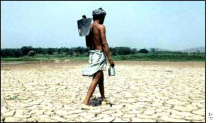 An Indian farmer walks across a parched, drought-hit field