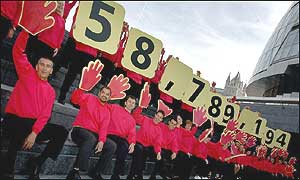 Volunteers display the UK's population figure