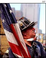 A firefighter carries the US flag to the highest point in the rubble of the World Trade Center after the 11 September attacks.