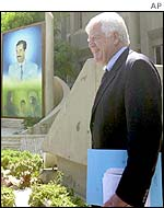 Representative Jim McDermott walks past a picture of Saddam Hussein
