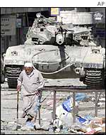 A man walks past a tank in Nablus