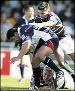 Daryl Gibson is tackled by Leicester's Steve Booth and Lewis Moody during Bristol's 25-20 win over the Tigers