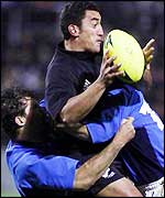 Daryl Gibson is tackled while playing for New Zealand against Italy
