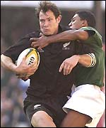 All Black Leon MacDonald is tackled by South Africa's Breyton Paulse